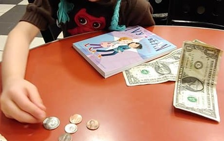 Luisa at table with money